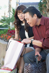 Couple sitting outside on Shopping Trip husband looking in wの写真素材 [FYI03643516]