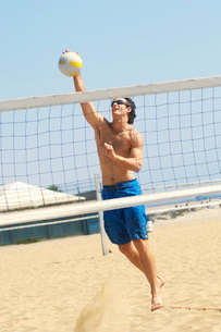 Young man jumping hitting volleyball over net on beachの写真素材 [FYI03643520]