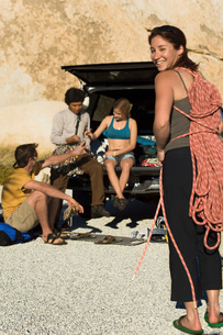 Rock climber holding rope with friends sitting by Truck  (poの写真素材 [FYI03643532]