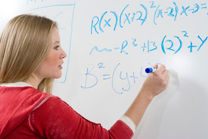 Female student writing maths equations on whiteboardの写真素材 [FYI03643546]