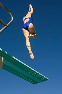 Female swimmer jumping on diving boardsの写真素材 [FYI03643585]