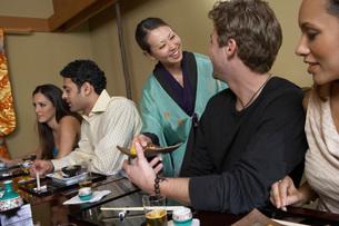 Waitress serving sushi to restaurantの写真素材 [FYI03643627]