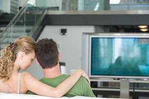 Young couple sitting on sofaの写真素材 [FYI03643666]