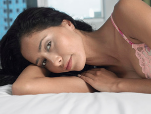 Woman in underwear reclining on bed head and shouldersの写真素材 [FYI03643689]