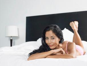 Woman in underwear reclining on bedの写真素材 [FYI03643690]