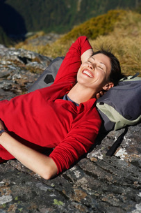 Woman laying on backpack on bouldersの写真素材 [FYI03643777]