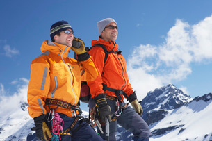 Two mountain climbers standing on peakの写真素材 [FYI03643790]