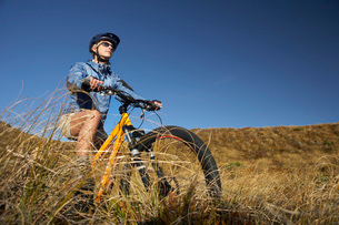 Woman riding bicycle in fieldの写真素材 [FYI03643794]