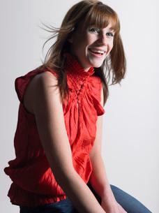 Woman in red top sitting in studioの写真素材 [FYI03643820]