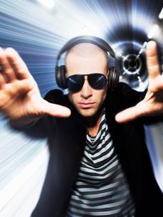 Man wearing headphones in front of tunnel effect view througの写真素材 [FYI03643876]
