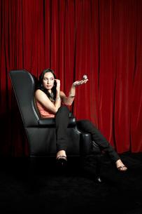 Stylish woman sitting leg over arm in wingback chair checkinの写真素材 [FYI03643914]