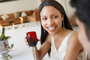 Young Woman Drinking Wine socialising at formal dinner partyの写真素材 [FYI03643948]