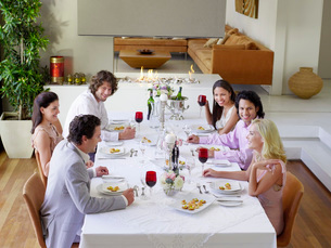 Friends sitting together at Dinner Party drinking and socialの写真素材 [FYI03643951]