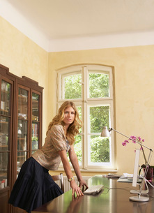 Young woman leaning on table in living roomの写真素材 [FYI03644059]