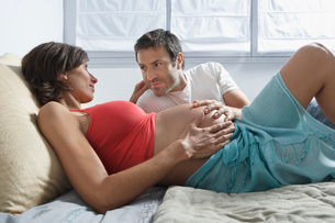 Man touching stomach of pregnant woman lying in bed in bedroの写真素材 [FYI03644104]