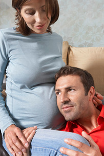 Man putting head on pregnant woman's stomach in living roomの写真素材 [FYI03644112]