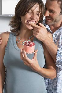Man feeding pregnant woman strawberry shortcake in kitchenの写真素材 [FYI03644131]