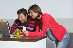 Man and pregnant woman using laptop to shop online at homeの写真素材 [FYI03644134]