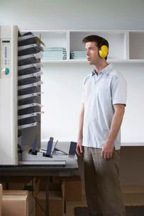 Man wearing headphones standing by photocopierの写真素材 [FYI03644170]