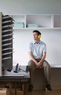 Man wearing headphones sitting by photocopierの写真素材 [FYI03644171]