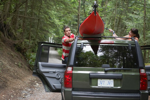 Man tying kayak on car roof in forestの写真素材 [FYI03644234]