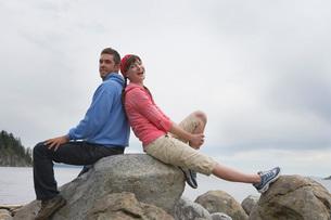 Couple sitting back to back on rocks by ocean portraitの写真素材 [FYI03644249]
