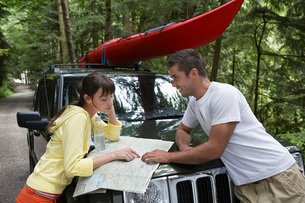 Couple observing map on car bonnet in forestの写真素材 [FYI03644254]