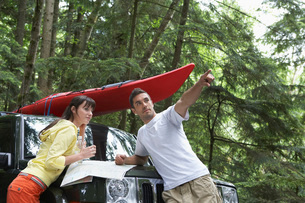 Couple with map on car bonnet in forest man pointingの写真素材 [FYI03644256]