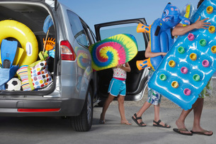 Father and two children (6-11) unloading beach accessories fの写真素材 [FYI03644268]