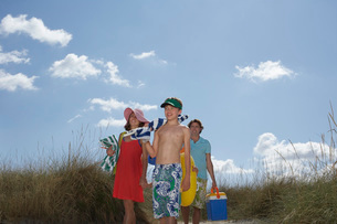 Parents with son (10-12) carrying beach accessoriesの写真素材 [FYI03644270]