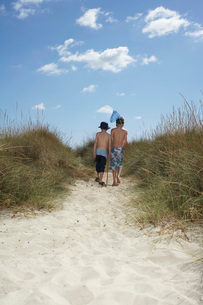 Two boys (6-11) walking in sand dunes with fishing net backの写真素材 [FYI03644271]