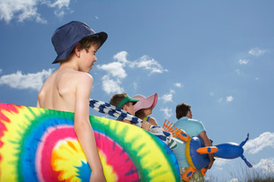 Parents with sons (6-12) carrying beach accessories back vieの写真素材 [FYI03644273]