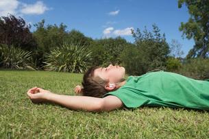 Boy (10-12) lying on grass listening to mp3 playerの写真素材 [FYI03644286]