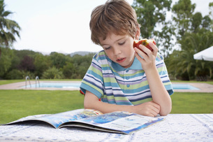 Boy (5-6) sitting at table reading and eating appleの写真素材 [FYI03644347]