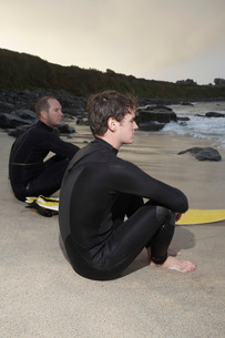 Two surfers sitting on beach looking at sea side viewの写真素材 [FYI03644416]
