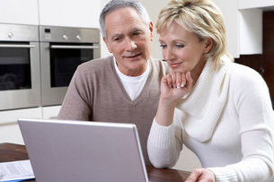 Middle-aged couple counting bills using laptop in kitchenの写真素材 [FYI03644439]