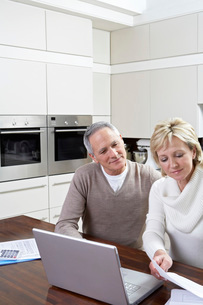Middle-aged couple working on laptop in kitchenの写真素材 [FYI03644440]