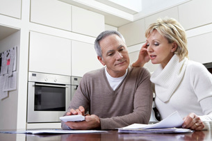 Middle-aged couple sitting in kitchen counting bills using cの写真素材 [FYI03644441]