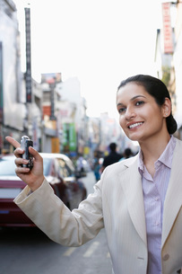 Business woman holding cell phone hailing taxiの写真素材 [FYI03644465]