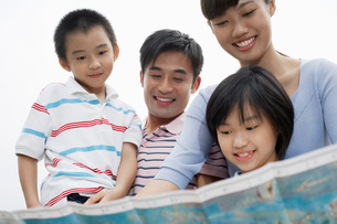 Family including boy and girl (7-9) reading map outdoorsの写真素材 [FYI03644534]