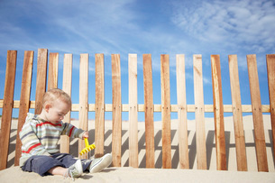 Boy (1-2) playing with beach rake by wooden fence on sand duの写真素材 [FYI03644541]