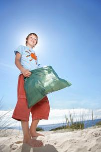 Boy (10-12) holding plastic bag on sand dune portraitの写真素材 [FYI03644542]