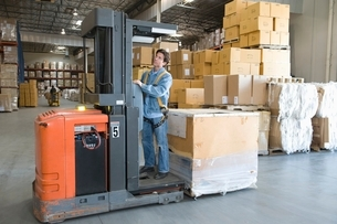 Man operating fork lift truck in distribution warehouseの写真素材 [FYI03644580]