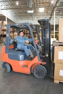 Man operating fork lift truck in distribution warehouseの写真素材 [FYI03644581]