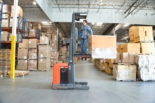 Man operating fork lift truck in distribution warehouseの写真素材 [FYI03644584]