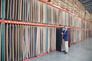Manager holding plywood in warehouseの写真素材 [FYI03644622]