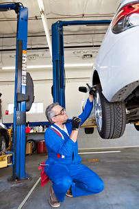 Man working on car tireの写真素材 [FYI03644653]