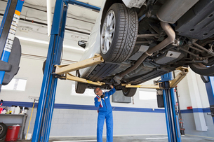 Low angle view of mechanic working under carの写真素材 [FYI03644659]
