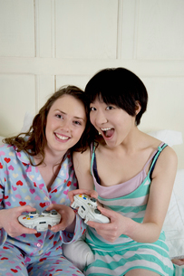 Two female friends playing video gameの写真素材 [FYI03644708]