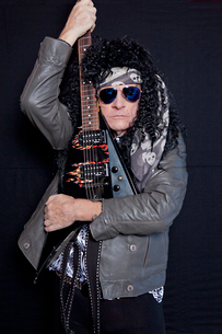 Portrait of senior male heavy rock metal guitarist over blacの写真素材 [FYI03644788]